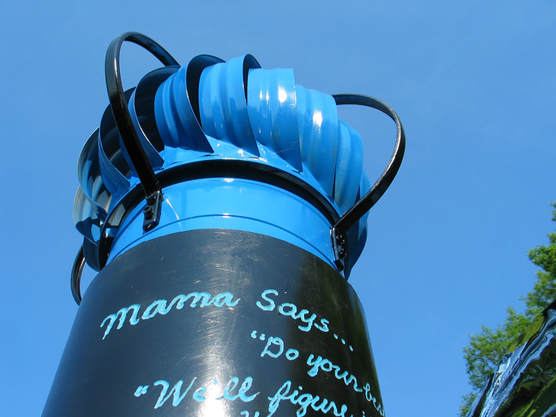 The top of Mama says, painted black and sky blue, showing part of the big plastic water pipe topped by a vent fan high above head height.