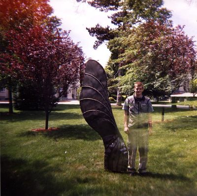 Square color photo double exposure showing Andy, my assistant, with part of his body disappearing, next to my eight foot tall steel maple seed.