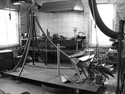 "The curved pipe suspended from the ceiling by chains, the five curved ""needles"" at one end and some of the scales already welded on to begin the pinecone that will be Strobus. Welding equipment, vent system and table in the background."