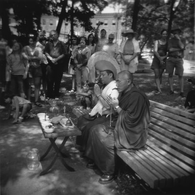Two Buddhist monks sitting on a bench beneath trees with a crowd behind them. They are blessing the collected sands from their former mandala.