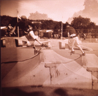 Square sepia-colored double exposure of a boy skateboarding in two positions at once in a skateboard park.
