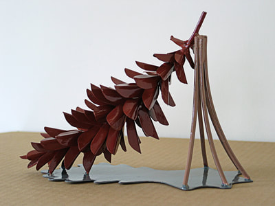 A maquette - a scale model - of Strobus. Made of painted copper. The pinecone is red, the five needles holding it up at one end are ocher and the shadow base is grey.