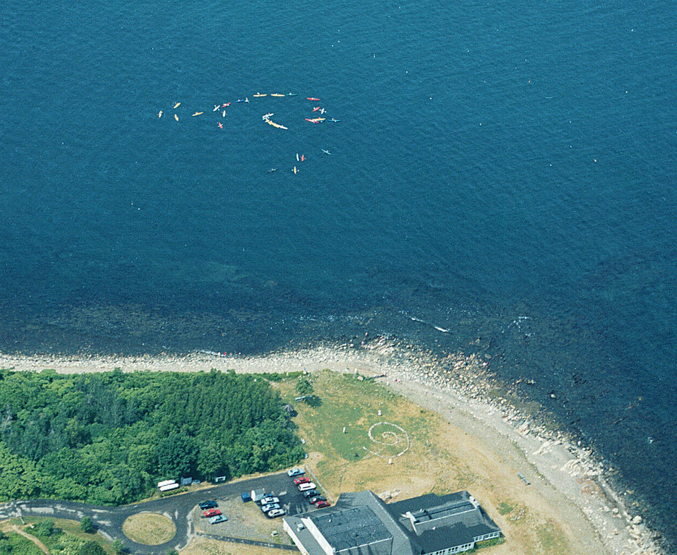 aerial photograph of thirty sea keayakers making a spiral on the bay near a huge stone spiral by the Seacoast Sicience Center in NH to suggest global ocean gyres.