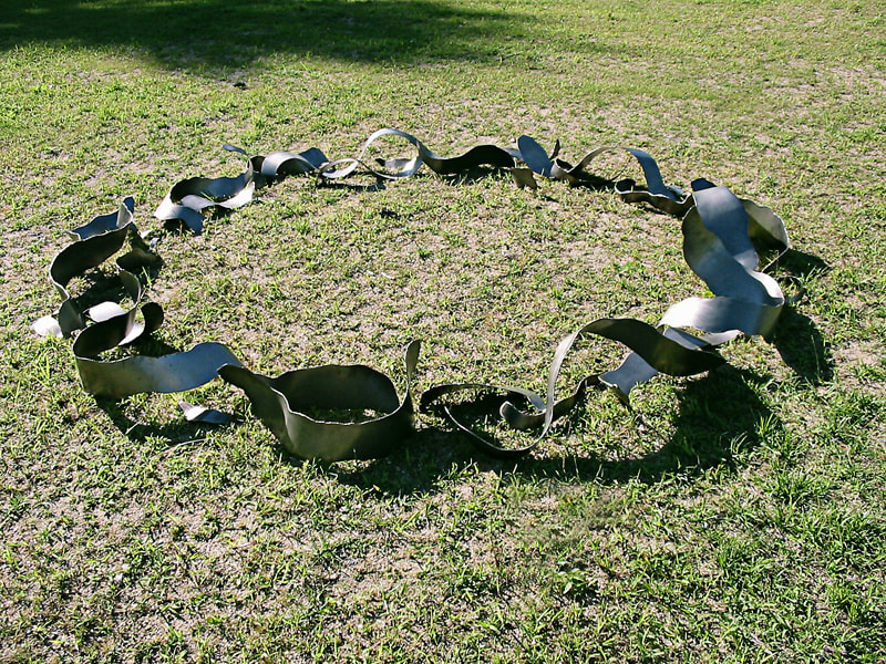 Twisted organically shaped steel ribbons arranged in a circle on the lawn of a sculpture venue.
