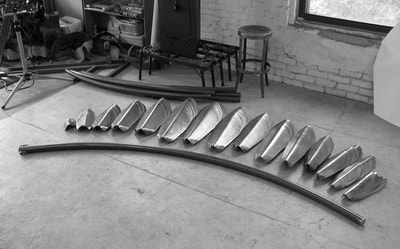 Seventy-five steel pinecone scales cut and bent, arranged on the floor next to the curved pipe that will be their core. Bottom of another sculpture in the background.