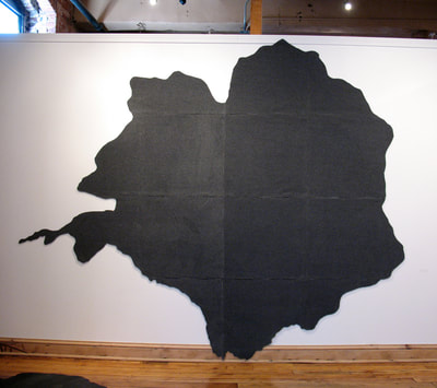 A large abstract shape made of dark grey Polartec fleece made from the footprint of a big silver maple tree on the white wall of the Beland Gallery. The footprint was made on Campagnone Common in Lawrence, MA. That tree was a witness to the Bread and Roses strike.