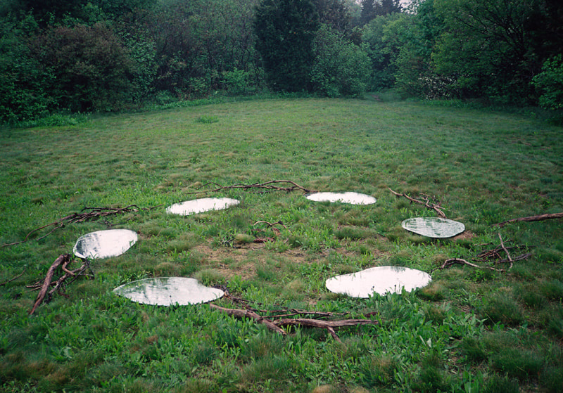 In a field surrounded by green forest, a ring of ovate mirrors reflect the sky suggesting pools of water.