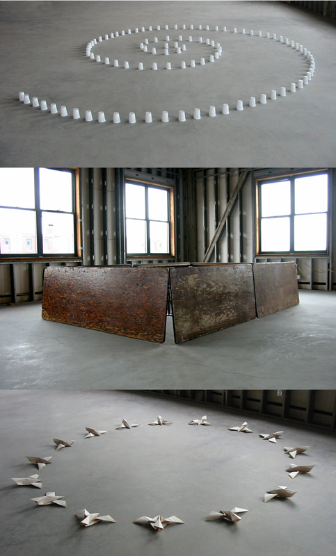 Three installations in a Boston building being rehabbed. Top: a spiral of white plastic cups on the grey floor. Center, a rectangle of old wooden tables echoing Richard Serra's art. Bottom: a ring of white origami songbirds on the grey floor.