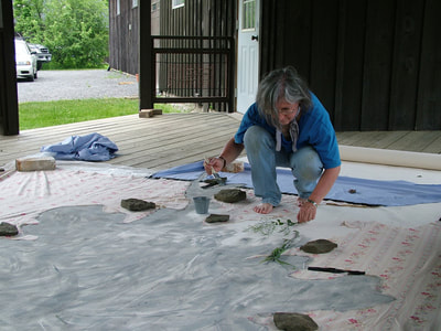 I crouch on the floor of an open air outbuilding of the Stone Quarry Hill Art Park, NY, while painting the stencil for Sugar Maple Footprint, NY.